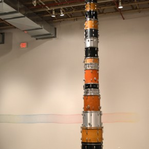 Eleanor King, Endless column (foreground), drums, steel cable, sound, 2011, 55.9 cm x 457.2 cm. Spinning Record, (background), coloured pencil on wall, 30.5 cm x 670.6 cm, 2012. Photo: Eleanor King, Courtesy of Diaz Contemporary, Toronto.
