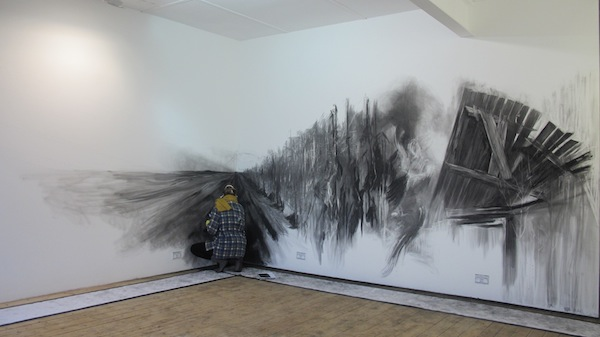 Katie Belcher depicted alongside her wall drawing at Queen Street Studios in Belfast, Northern Ireland, 2013.