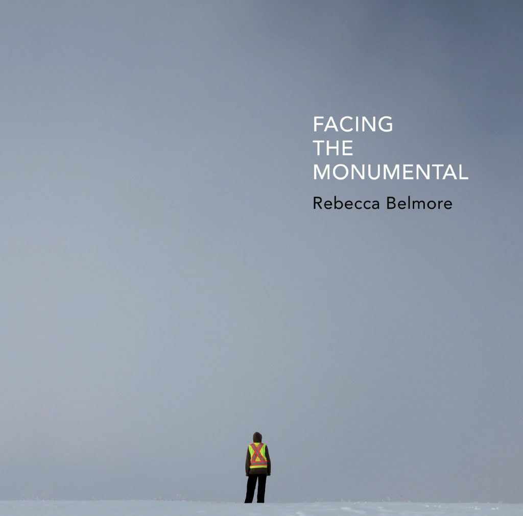 """A person in a reflexive vest stands on a grey-blue sky line, small at the bottom. The title, Facing the Monumental, is printed in white all-caps with """"Rebecca Belmore"""" in black directly below."""