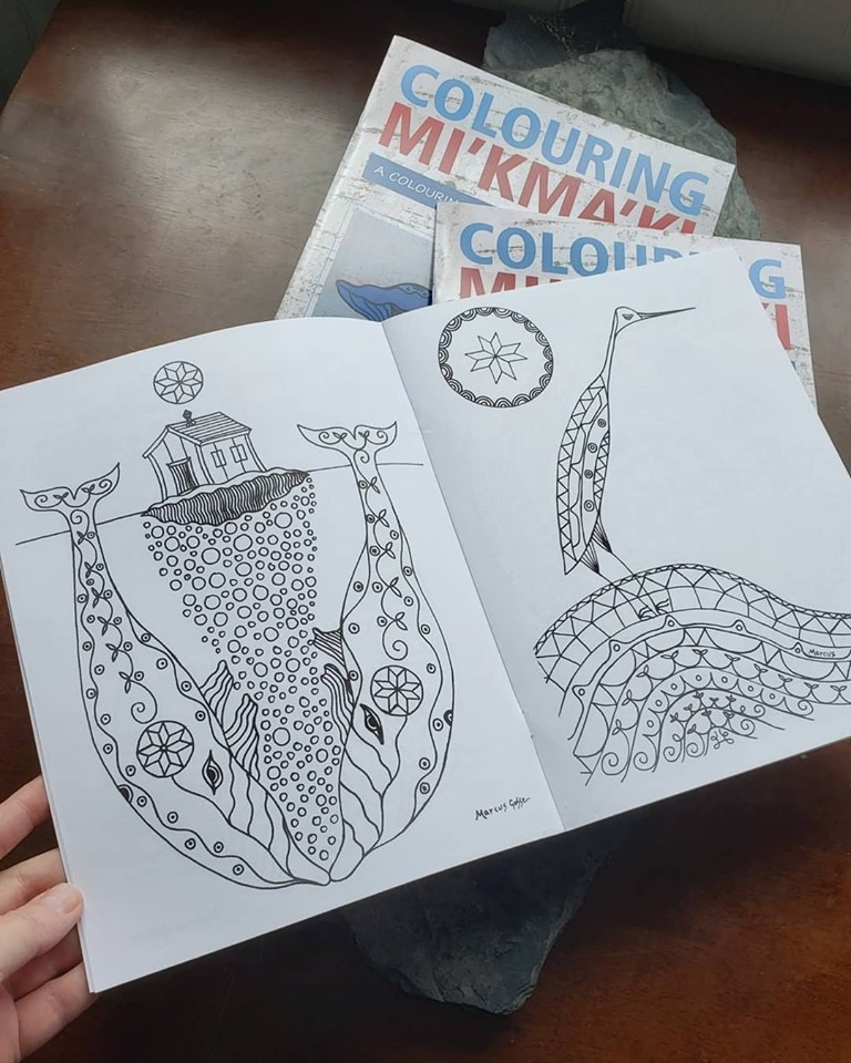 """A book is held open showing black line art of two whales with a house between them on one page, and a crane on the opposite. Two copies of """"Colouring Mi'kma'ki"""" are stacked in the background."""