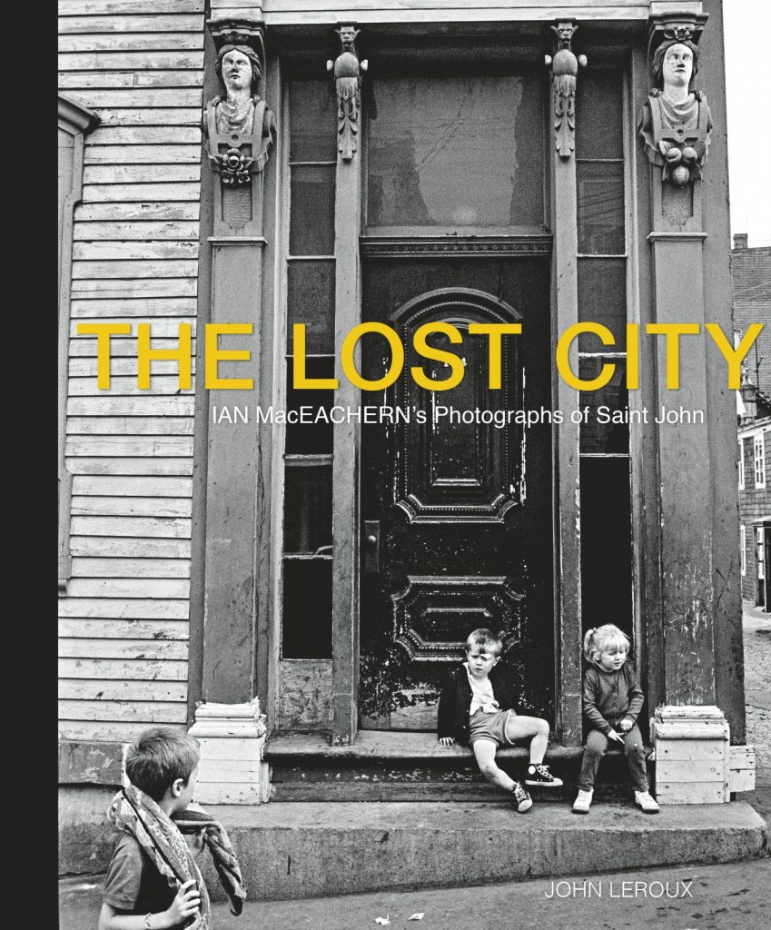 "A black and white photograph of two children sitting on the front step of a building , with a third child looking on. The Lost City is printed across the centre in yellow all-caps with the subtitle in white printed below: ""Ian MacEachern's Photographs of Saint John"". The author's name, John Leroux, is printed in white all caps in the bottom right corner."