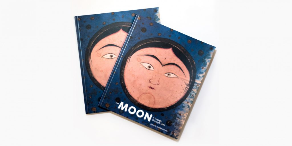 Two books lay stacked on top of one another, both featuring a round face on a blue background. White text reading The Moon: A Voyage Through Time is printed at the bottom.