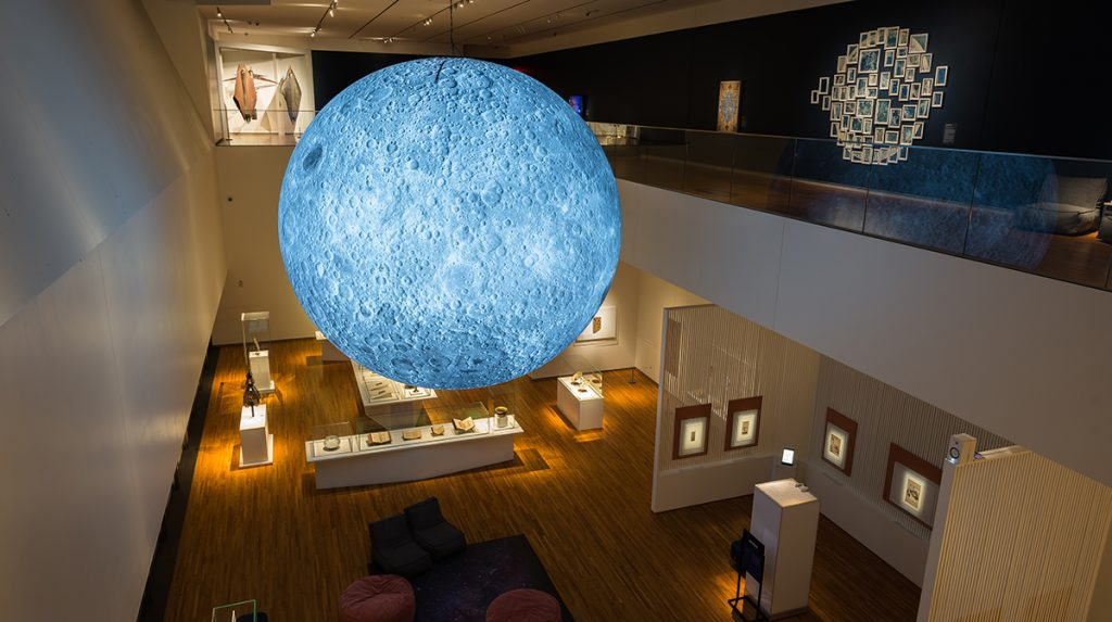 A glowing blue moon hangs across from a second-story balcony in a darkened gallery. Various art works are visible both on this second story and below in the first.