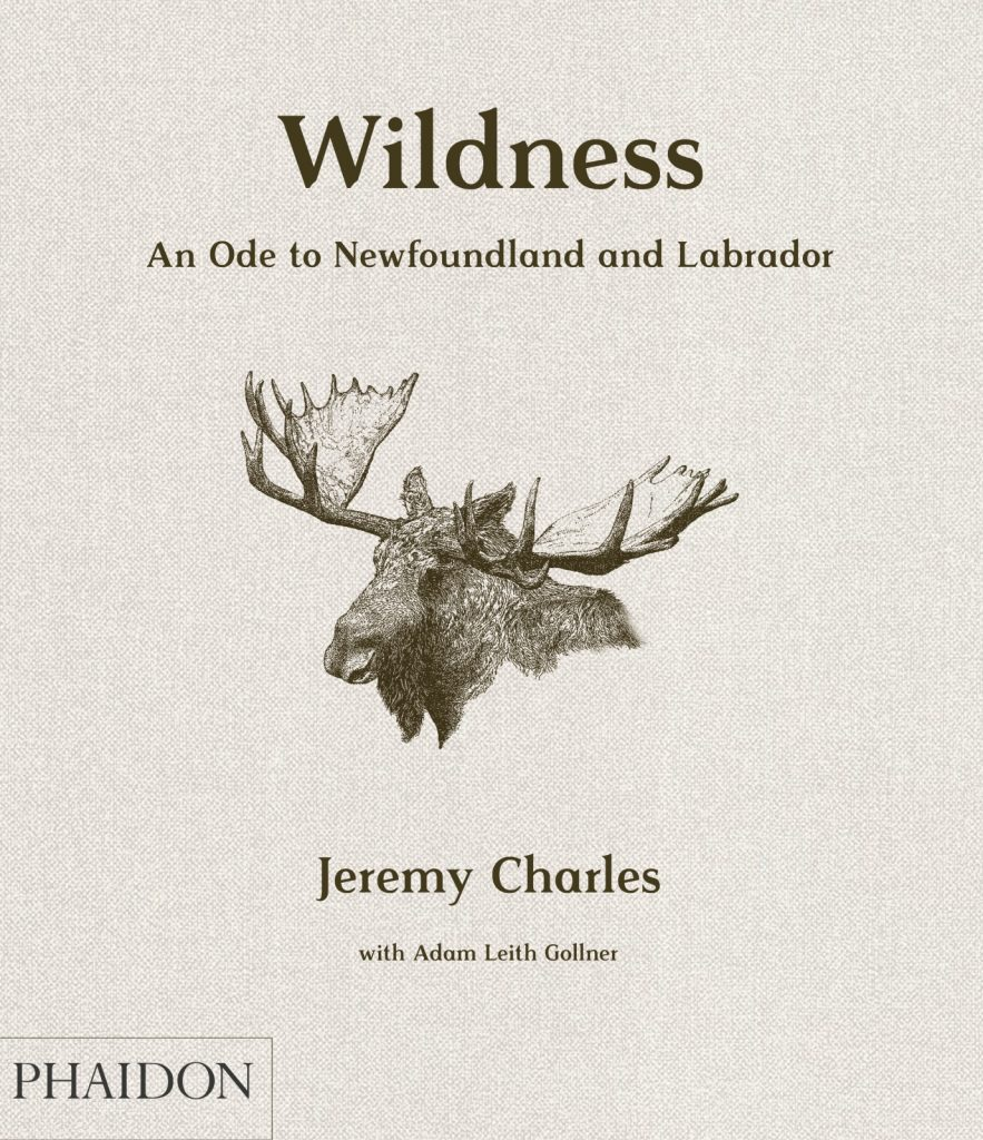 "A beige fabric background featuring a brown-black moose head in the centre. The title ""Wildness: An Ode to Newfoundland and Labrador"" is printed above and the authors ""Jeremy Charles with Adam Leith Gollner"" printed below, the second name much smaller than the first. The publishing company's logo - Phaidon in all-caps in a rectangular box - is place in the bottom left corner."