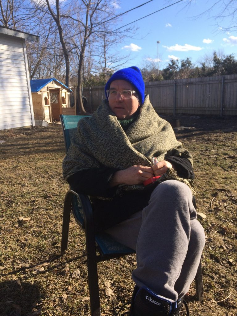 The poet RM Vaughan sitting in a lawn chair, bundled in a blanket.