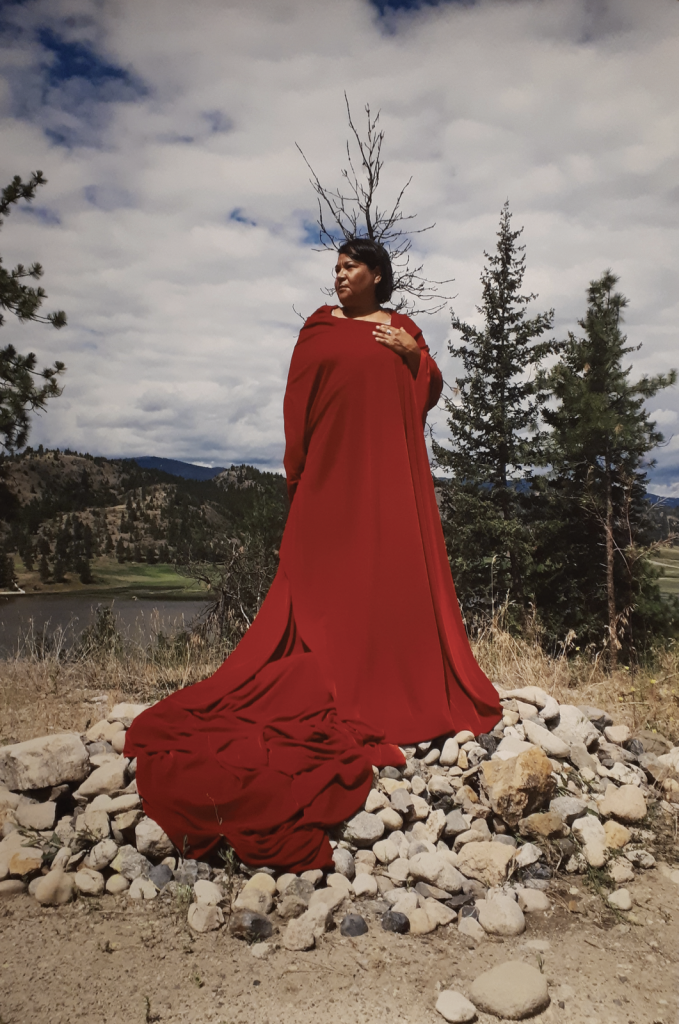 Lori Blondeau, regal, stands dressed in a long red cloth wrapped into dress or robe, on a pile of rocks, in a landscape of trees, hills, and water. The artist looks to the side, left hand on chest.